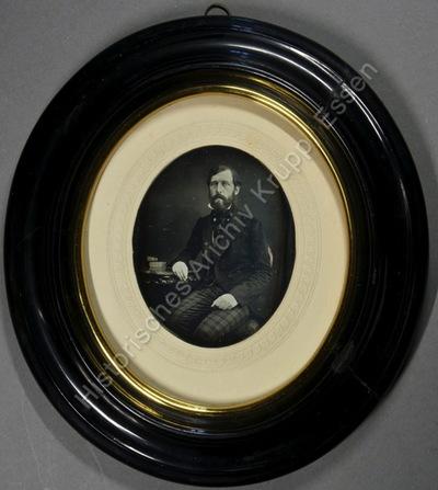 Dreiviertelportrait von Ernst Eichhoff am Tisch sitzend. Auf dem Tisch liegen neben seinem Arm zwei Bücher.