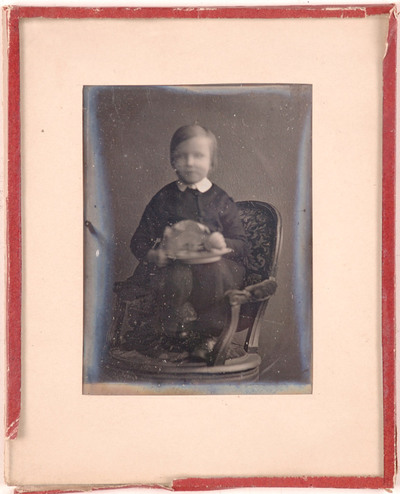 Portrait of an unknown young person, seated on the armrest of a chair