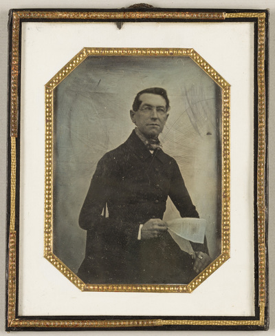 Portrait of a man seated, in his right hand holding a sheet of paper covered with writing