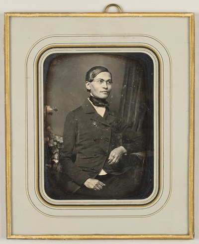 Portrait of a young man - Filip Piwonka, seated, wearing glasses, resting his left hand  on a table. Flower decoration is visible on the table at the left edge. In the back is hanging drapery.