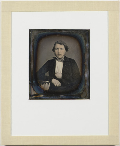 Portrait of a young man with sideburns sitting with a hand in his coat and leaning on a table with a tablecloth.  Written on the back is Johan Lossius, 1857. Assuming this is Johan Jørgen Lossius (27.09.1835 -), he would be approximately 22 years old when this picture was taken.  Johan Jørgen Lossius was married to Marie Maisen Lossius (born Gram, 24.02.1839 - 24.03.1910).
