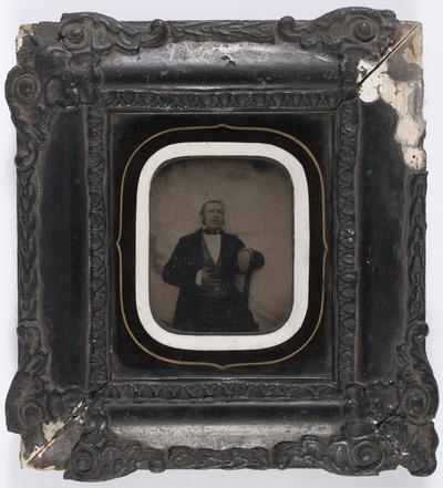 portrait en demi-hauteur d'un homme assis en studio, une main posée sur le ventre, portant une montre à gousset, réhaussé