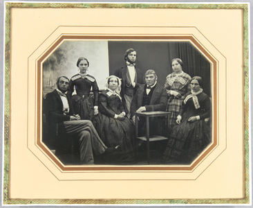 Familie mit 7 Personen, drei Männer, vier Frauen, vor einem Vorhang im Hintergrund, der links die gemalten Stadtansicht Lübecks frei gibt.