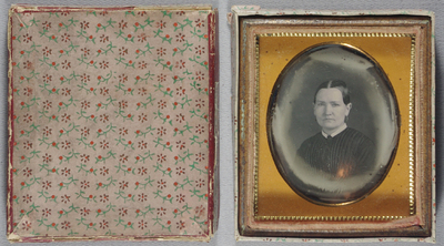 Label on back, hand-written 'Wife of Robert Potter.' / Has original cardboard presentation box with lid. Top and sides decorated with a pink paper with small sprig and flower design in red, green and maroon. Lid decorative paper partly covers a plain red paper beneath. Style is Anglo-American but with a circular metal suspension loop at the top of the back of the image.