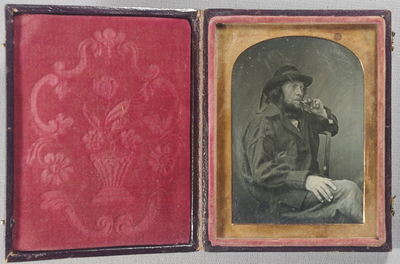 Three quarter length portrait of a seated workman (?), his left arm over the back of the chair. His legs are crossed and his right hand rests on his thigh. He is smoking a short stubby pipe held in his left hand. He has a long hair, a beard (chin curtain). He has a large dark jacket, white shirt, and a dark hat with a dark band which hangs down the back as ribbons. He wears a ring on the little finger of his left hand