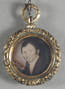 Daguerrian Jewellery: Gold locket possibly gold plated silver (rolled gold) with decorative pattern work housing a daguerreotype portrait of a man resembling a photo of a painting. Gold metal backing cover that appears to open but has not been opened. It may contain hair.
