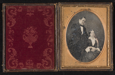 Portrait of a couple, three-quarter length and half figure, the woman is seated on a chair with her hands on the lap, and the man is standing on her right side. Cheeks, lips and ribbon are hand-coloured pink. Jewellery hand-coloured with gold.