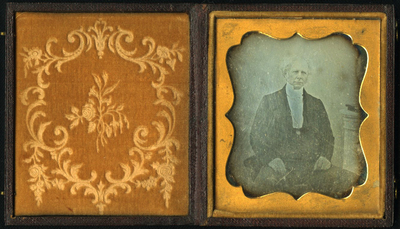 Seated three quarter length frontal portrait middle aged man with wispy white hair. Open dark jacket. High collared white shirt with medaillon. Hands resting in lap. Short column on right side with two books.
