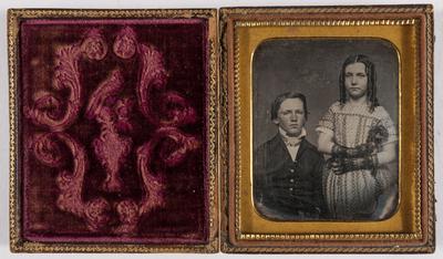 Portret van een zittende jongen en een staand meisje, het meisje heeft pijpenkrullen, draagt een jurk met bollenmotief, en zwarte handschoenen. Ze heeft een bloem of veren vast