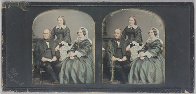 Group portrait of a three people, two seated (man and woman) and a younger woman standing behind. The man wears a dark suit (jacket, waistcoat, trousers) with white shirt and dark cravat. He has blond, receding hair and bushy sideburns. He sits on an ornate chair (gold highlights on leg) and holds a piece of paper, looks like a letter, in his hands. The younger woman standing behind him has her left hand on his left arm,: she wears a dark dress buttoned down the front, with a broad lace collar, lace cuffs or under-sleeves, a dark velvet bow at the neck with a brooch. Her hair (dark blonde) is gathered behind her head. A black velvet bow with a jewel is tied around her left wrist as a bracelet. The seated woman wears a lace cap with lappets down the back, a blue and black striped dress with gold buttons down the front. Her hands are folded on her lap; she holds a small white book. She also has a broad lace collar with a brooch at the neck, and lace cuffs; a gold ring is on her left hand and she wears a gold bracelet. To her right is a draped textile, white lace and gold, perhaps a shawl. The painted backdrop shows the edge of a column and base, and a wainscot. Hand coloured, gold highlights.