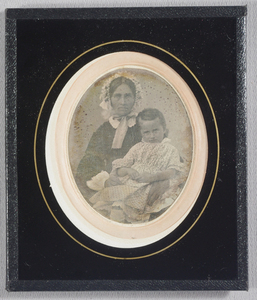 Half-length seated woman with young boy on her lap. She wears a black dress with white collar and cuffs, and bonnet with a middle parting. The boy wears a pale breeching dress with knee-length socks.