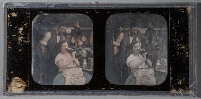 Stereo portrait of a young woman and a man. Woman has a bottle in her lips. Man stands behind the woman,  pans and pots in the back ground. Partly coloured.