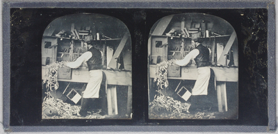 Stereo view of a carpenter in his workshop. He is planing a piece of wood, with wood-shavings on the bench and floor. A shelf at head height is bending under the weight of equipment including vice, squares, clamps, mallet and other tools. Behind him on the wall above the bench are chisels, angles, pliers, a hammer upright,  saw etc. He wears dark trousers dark waistcoat, white shirt, white apron and paper hat. He has dark hair and sideburns.