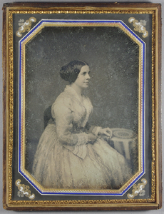 Three quarter length portrait of a young woman, seated on a wooden chair (the back is partially visible) facing to her left. She wears a pale patterned dress. Her hair is straight and covers the ears, it is held in a bun at the back, with a curl visible on the cheek. She has a lace collar, also running down the front of the dress. Frilled, gathered decorative textiles on ends of the sleeves. Her left hand rests on a circular table covered with a cloth, her right hand on her lap. Hand coloured.