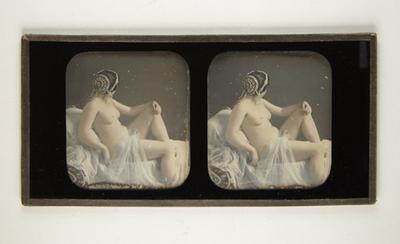 Weiblicher Akt auf einem mit Tüll dekoriertem Sofa, den Kopf abgewendet, mit reichhaltigem Kopfschmuck aus Perlen