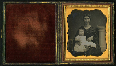 Three quarter length frontal portrait of lady in black with baby in her lap. Lady with short black hair loped over ears wears low necked shiny dress with brooch. Baby in long cotton dress has blured and axious face. Half leght grecian column in background.