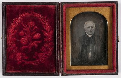 portret van een man, grijs haar, handen in elkaar, draagt een zwarte mantel