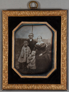 Portrait of dean August Lindfors and his wife Fredrika b.Standendersköld and children August and Tullia, exterior portrait, a fence and bushes on background.