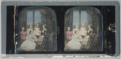 Hand coloured family seen featuring a woman, three girls and one boy. The woman is seated, with children either kneeling or standing around her. The woman wears a dress with a lace collar, neck bow and cap, and chain around her neck. Her hair is worn with a middle parting. The oldest girl kneels by the woman, wearing a long sleeved dress, lace collar and cuffs, bracelet on her right hand and necklace around her neck. Her hair is in a middle parting and tied back with a bow. The middle girl is standing behind the kneeling girl wearing a long sleeved dress, lace collar. Her hair is worn in a middle parting, tied back with a bow. The youngest girl is seated on a high chair in between the middle girl and woman, holding the woman's right hand with her left, wearing a short sleeved dress. Her hair is worn in a middle parting and loose above her shoulders. The young boy on the left stands next to the middle girl and wears a tunic fastened at the waist with a belt. His hair is worn with a short fringe. His left hand rests on the shoulder of the middle girl. Studio background includes, patterned wall paper, patterned curtains, and fringed pelmet. Window pains lead to a painted background.