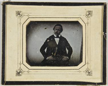 Herr mit einer Uhrenkette an der Weste, die Arme auf dem Oberschenkel abgestützt, sitzend, Halbfigur, teilkoloriert.