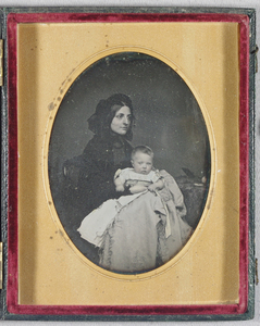 Portrait, three quarter length, of a seated woman with a baby in her lap and one hand around its waist. She wears a dark dress and a bonnet and has straight hair in a middle parting in front of it. She is seen in three quarters profile and the baby looks straight ahead. It is wearing a light coloured dress and coat. There is a table that has some objects on it on the right, and part of a chair back visible on the left..