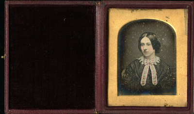 Head and shoulder tinted portrait of beautiful young woman with ribbon looking to the left. She wears thick hair luped her ears.