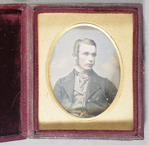 Head and shoulders portrait of a young man with straight fair hair, side parting, sideburns. Fancy waistcoat, dark jacket, watch chain, broad lapels. Hand tinted with gold highlight on tie-pin, looking to his left.