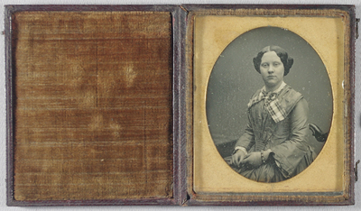Half length view of a seated young woman with her hands in her lap. Wavy dark hair frames her face. She wears a mid-colour dress with flared sleeves, and white cuffs.  She has a broad plaid ribbon tied in a bow around her collar, also a white lace collar. She has two bracelets, one beaded, the other gold.  Part of a rectangular table is visible, as is the carved wooden back of her chair. Gold highlights.