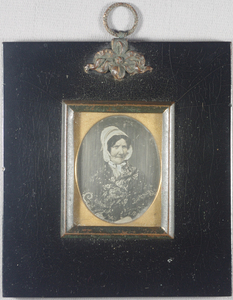 Half-length portrait of a seated woman with the tops of her wrists visible resting in her lap. She wears a floral patterned shawl over her dress (dress not visible). Her hair is worn in a middle parting with a bonnet, tied around the chin with a ribbon. Plain background.  Plate set in black japanned frame with black metal sight edge. Suspension hoop with banner style hanging mechanism with the words BEARD PATENTEE (Richard Beard).