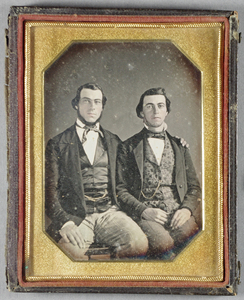 Three-quarter length portrait of two seated young men. The young man on the left wears striped trousers, waistcoat with pocket watch chain, jacket, shirt and cravat. His receding hair is in a side parting and he has a chinstrap beard. His right hand is on one knee and his left arm around the shoulders of the other sitter. The young man on the right is wearing trousers, floral patterned waistcoat with pocket watch chain, jacket and bow tie. His hair is in a side parting and is clean shaven. His hands rest in his lap. The watch chains and their lips and blush are hand coloured. Plain background.
