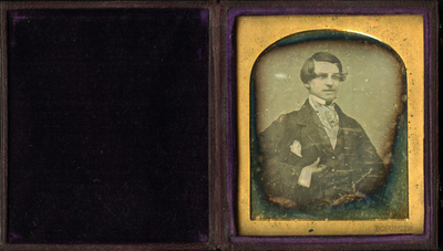 Half length portrait of a young seated man looking to the right.