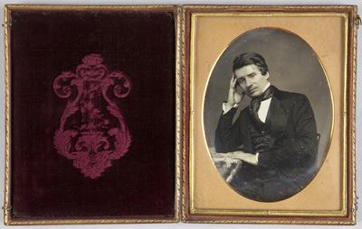 Mann an einem Tisch sitzend, den Arm aufgestützt und die Hand an die Stirn gelegt, Halbfigur.