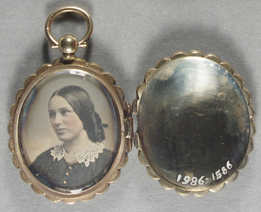 Daguerrian Jewellery:  1986-1586 - Gold locket containing a portrait of a lady with lace collar. The cover (top of the locket) has a centrally engraved initials surrounded within an oval within an oval surrounded by a grid-like radiating decoration, there is a scalloped shape going round the edges of the tray.  The cover detaches from the tray via a press clasp centrally located on the right side of the tray.