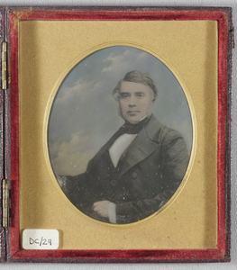 Half length portrait of a seated man, facing the camera, his body turned to his right. Against a painted backdrop of clouds. He wears a dark jacket, white shirt, dark cravat. His hair and sideburns are going grey. Hand coloured.