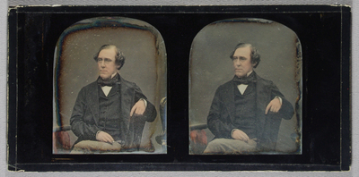 Half-length portrait of a man, seated facing slightly to his right, legs crossed. His left arm rests on the back the chair, his right hand on his left thigh. He wears a dark jacket, waistcoat and cravat, with a white shirt, and checked trousers. He is clean-shaven, with dark but greying hair. He has a gold ring on the little finger of his right hand. The edge of a table is visible to his right, and the edge of an ornate piece of furniture to his left. Hand-coloured.