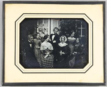 Familienbild mit 7 Personen, Großmutter, Eltern und Kinder. Außenaufnahme vor zwei geschlossenen Fenstern und rankenden Pflanzen im Hintergrund.