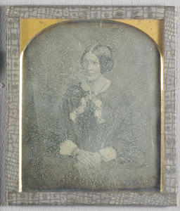 Half length portrait of a woman, seated with her hands together resting on her lap, looking to her right. She wears a dark dress with a white lace collar and cuffs, and decorative ribbons crossed at the front.