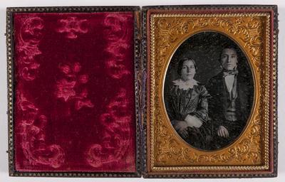 portret van een man en een vrouw, zittend, vrouw draagt donkere jurk met witte kraag en ingekleurde broche, witte ondermouwen, man draagt gestreepte strikdas
