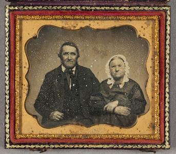 Puolikuvassa iäkäs pariskunta istuu kylki kyljessä, poskipäihin on lisätty punertavaa sävyä. Naisella on silmälasit ja päässä pitsisomisteinen hilkka.