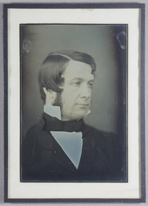 Pass partout mounted daguerreotype. Head and shoulders portrait of a middle aged man facing the viewer's right. The man wears a button jacket, white shirt with high collar and a black bow tie. He has a side parting and side burns. Plain background.