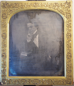 Possibly the largest surviving, vintage daguerreotype plate in the world.  Either a daguerreotype that has been rephotographed or possibly a daguerreotype print from a large negative. 'In March 1849, J.J.E. Mayall exhibited what he asserted were the largest daguerreotype portraits ever taken in England. During this period, there were rival claims by other photographers that they had also made giant daguerreotypes. Mayall quickly placed an advertisement in 'The Times' re-iterating his declaration that he had produced the largest daguerreotype portraits and added drily, As no other pictures have been taken in any degree approaching these in size, all recent advertised pretensions can only be intended to mislead the public.  In 'The Times' newspaper of 1st July 1850, Mayall claimed that he could take portraits from 30 inches in length down to the microscopic size. source http://spartacus-educational.com/DSmayall.htm  The sitter bears a close resemblance to the self-portrait of Mayall shown on http://spartacus-educational.com/DSmayall.htm and it seems likely that this is another self-portrait taken seven years later.