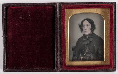 Portret oudere vrouw, donkere jurk met gestrikte kapmantel  buste, zittend, ingekleurde gouden halsketting; handen niet zichtbaar