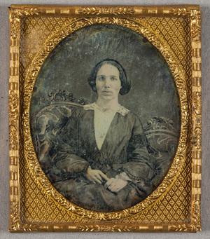Puolikuvassa nuori tummahiuksinen nainen. Hänellä on yllään asuste, jossa on pitsisomisteita hihoissa ja kauluksessa.  Nainen istuu sohvalla tai nojatuolissa, jonka koristeellinen selkämys erottuu naisen takaa.