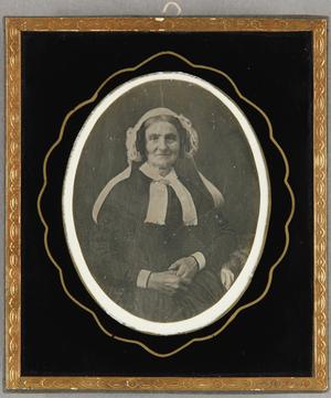 Ältere Frau mit weißer Haube und einer weißen Halsschleife, Halbfigur sitzend.