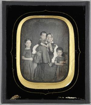 Junge Frau sitzend mit drei Kindern. Ein Kind steht auf ihrem Schoß, die beiden anderen rechts und links daneben.