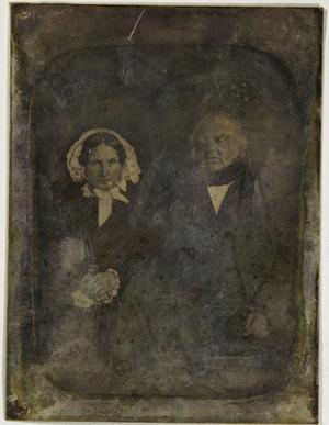 Älteres Ehepaar sitzend, sie trägt eine weiße Haube.