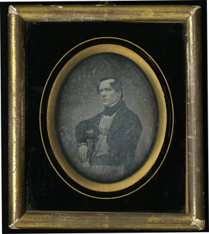 Half length portrait of seated middle aged clean shaven man turned left. One arm leaning on chair back the other on his lap.