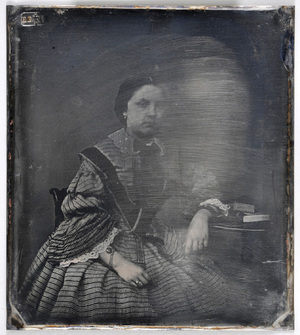 Portrait of a young woman with book on table