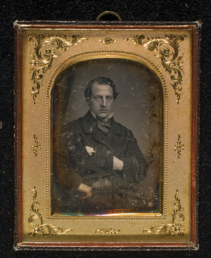 Portrait of a man, half figure, seated. His left arm hidden under his coat. Right arm resting on his hip. Wearing a ring on his little finger.