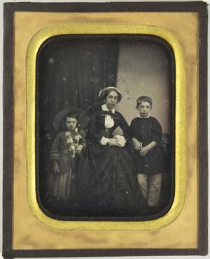 Frau mit einem flachen weißen Hut, sitzend, zu ihren Seiten ihre beiden kleinen Kinder, das Mädchen mit einem großen Hut, der Junge hält ein Buch in der Hand, Ganzfigur.